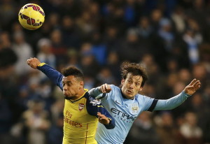 Arsenal's Francis Coquelin and Manchester City's David Silva jump for the ball during their English Premier League soccer match in Manchester