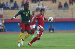 Pesepak bola Timnas Indonesia senior Tantan (kanan) berebut bola dengan pesepak bola Timnas Kamerun Bedimo Nsame Henri (kiri) pada laga persahabatan di Stadion Gelora Delta Sidoarjo, Jawa Timur, Rabu (25/3)