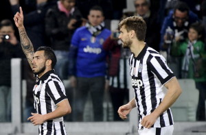 Juventus' Carlos Tevez celebrates with his team mates Arturo Vidal and Fernando Llorente after scoring against Empoli during their Italian Serie A soccer match in Turin